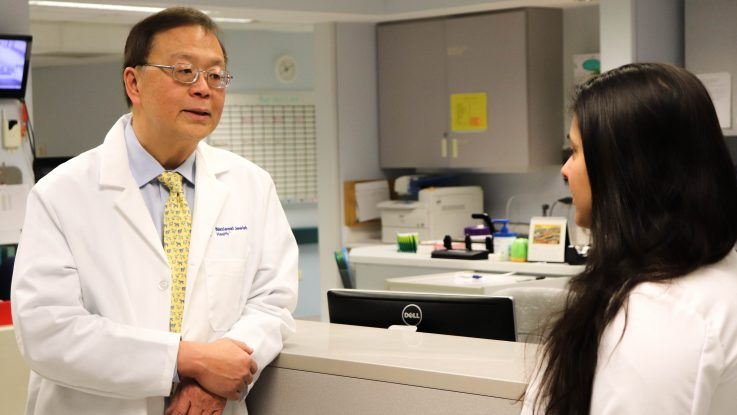 Donald Leung, MD consults with a colleague at National Jewish Health. Dr. Leung is leading a clinical trial to test a skin lotion containing beneficial bacteria that kills harmful bacteria on the skin of eczema patients.